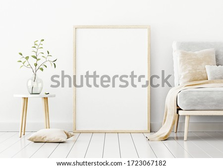 Poster mockup with vertical frame standing on floor in living room interior with sofa, beige pillow and branch in glass vase on empty white wall background. 3D rendering, illustration.