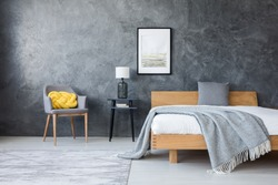 Poster on concrete wall above stool with lamp and wooden bed in dark bedroom with yellow pillow on a chair