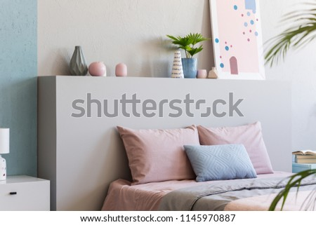 Poster on headboard of bed with pink pillows in bedroom interior with plants. Real photo #1145970887