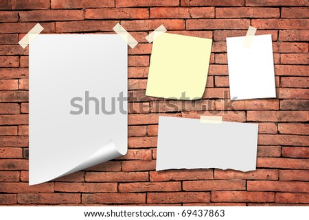 Poster paper and white paper notes. Stick tape on the orange brick wall.