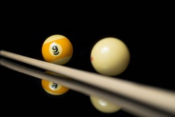Poster photo for tournaments, Shot on the nine ball in pool, billiard balls, white cue ball and yellow Nr. 1 ball on a black organic glass with reflections before tournament in europe, usa.