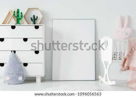 Poster with mockup between white cradle and cabinet in child's room interior. Real photo. Place for your poster