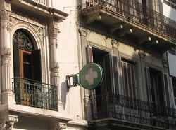 Poster with the classic pharmacy sign on a facade of an old house. Round vintage poster with a green cross on the wall of a street medicine store building illuminated by sunlight.