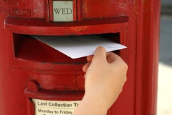 posting a letter to red british postbox on street