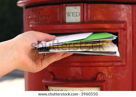 posting many letters to red british postbox on street
