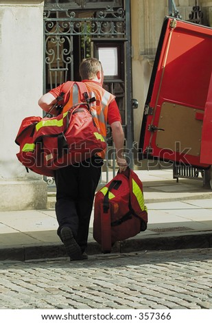 Postman carrying several heavy delivery bags