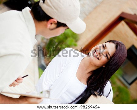 Postman delivering a package to a woman at home