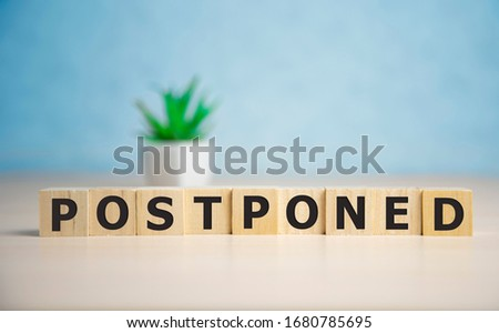 Postponed - words from wooden blocks with letters, postponed concept, top view background Stockfoto ©