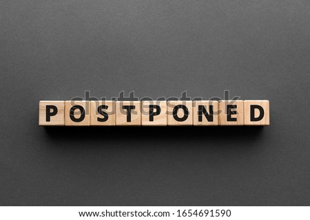 Postponed - words from wooden blocks with letters, postponed concept, top view gray background Stockfoto ©