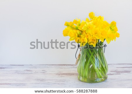 Posy of bright yellow daffodils on white wooden table with copy space