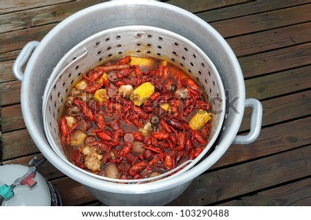 Pot And Basket Of Hot Boiled Louisiana Crawfish With Potatoes,Corn, Garlic, Mushrooms  And Sausage