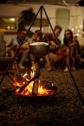 Pot is over campfire, friends on picnic at camping