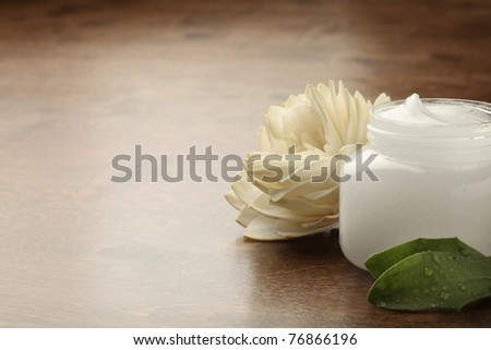 pot of cosmetic creme on a wooden surface - stock photo