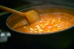 Pot of gravy or soup while cooking on the stove and is stirred to achieve the perfect cooking to be served.