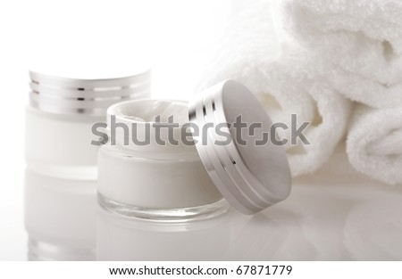 pot of moisturizing face cream and bath towels