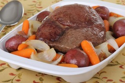 Pot roast with carrots, onions and potatoes in a serving plate