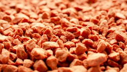 Potassium chloride is a red mineral fertilizer close-up. Red background of fertilizer potassium chloride. Texture of granular potassium chloride is red. Macro.