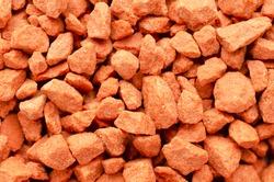 Potassium chloride is a red mineral fertilizer close-up. Red background of fertilizer potassium chloride. Texture of granular potassium chloride is red. Macro texture. Background mineral fertilizers.