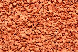Potassium chloride is a red mineral fertilizer, top view. Red background of fertilizer potassium chloride. Texture of granular potassium chloride is red. Background mineral fertilizers, top view.