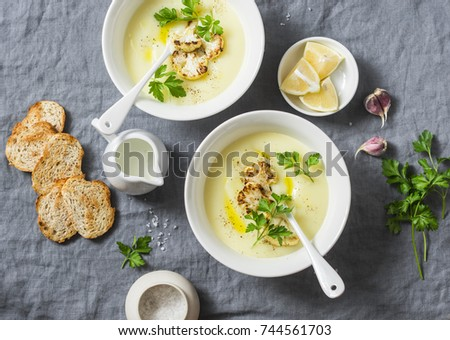 Potato cauliflower soup puree on a gray background, top view. Vegetarian healthy food concept