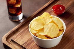 Potato chips in a bowl with dip sauce on wooden service tray and glass of coke. Close up view