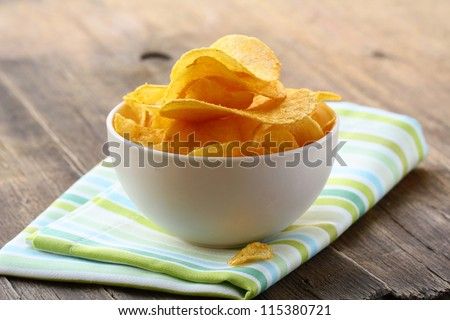 potato chips in a white bowl on a wooden table