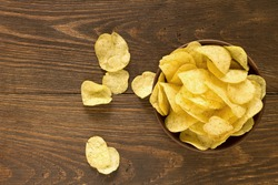 Potato chips in bowl on a wooden background, top view. Salty crisps scattered on a table.