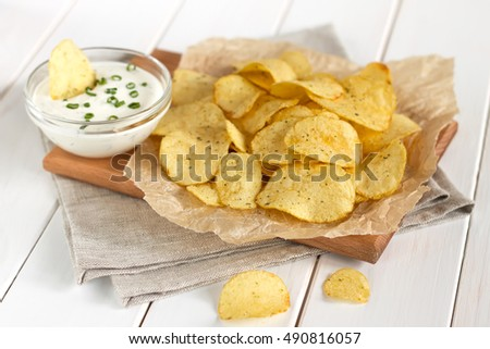 Potato chips on a parchment on a table. Concept of unhealthy food.