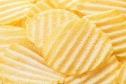 Potato chips pattern. Yellow corrugated salted potato chips as food background. Chips texture, studio photo, close up