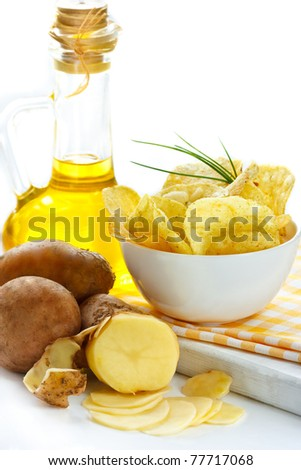 Potato chips, raw potato and jug of olive oil.