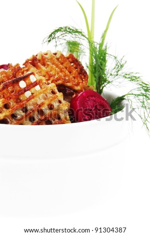 potato chips served in white bowl with small pickled eggplants isolated over white background