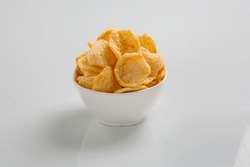 potato crackers chips in a wicker bowl on old kitchen table Bowl of home made potato chips served with mustard, rosemary, fleur de sell salt on stone background. Top view. Potato chips isolated on a w