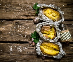Potato food . Baked potatoes in foil on a wooden table . Free space for text. Top view