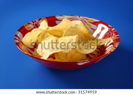 Potato fried chips on red plate over blue background