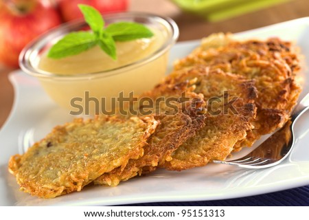 Potato fritters with apple sauce (Selective Focus, Focus on the front edge of the fritters in the front)