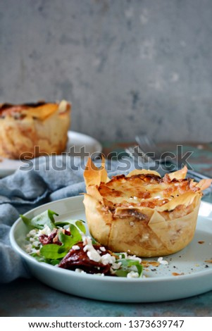 Potato gratin baked in filo dough, with crispy cheese crust and with a salad of arugula, sun-dried tomatoes and cheese on a blue background. A dish of french cuisine