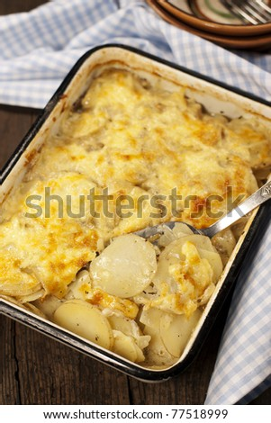 Potato gratin dauphinoise in the pan on rustic background