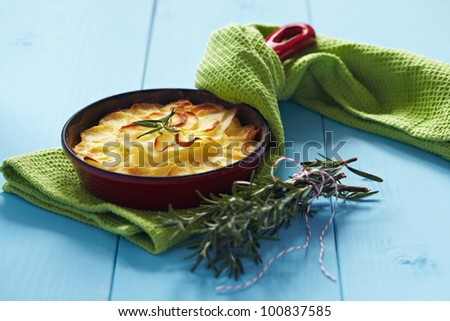 Potato gratin with rosemary in a small red pan