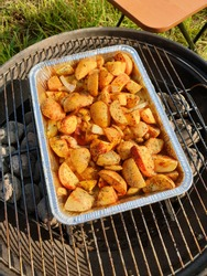 Potato in foil dish on charcoal barbecue grill