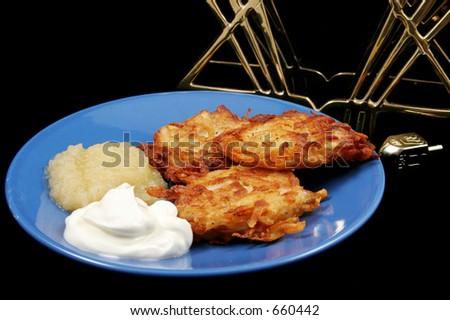 Potato latkes for Hanukah with a menorah and a dreidel on a black background.