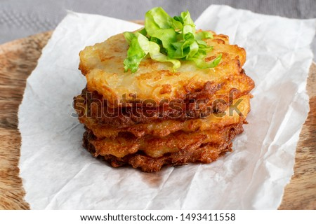Potato pancakes, draniki, deruny, potato latkes, latkas, irish cakes, raggmunk or boxties on wood plate. Fried grated vegetable pancakes or potato fritter with onion on rustic background