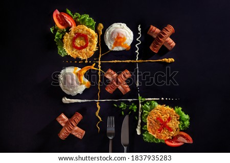 Potato pancakes, poached egg with yolk splash and fried sausages like tic-tac-toe board game concept on dark background with copy space. Grid is divided by mustard and mayonnaise Foto stock ©