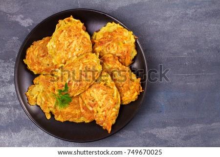 Shutterstock Potato Pancakes. Vegetable fritters. Latkes on black plate. View from above, top studio shot, horizontal