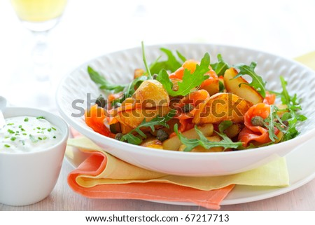 Potato salad with smoked salmon,capers,rocke t and sauce - stock photo