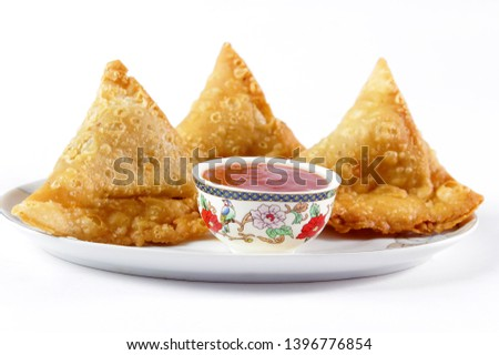 Potato samosa on white background, Traditional indian or pakistani ramadan food, Ramzan iftar meal, Spicy street food, Famous snacks in asian country.