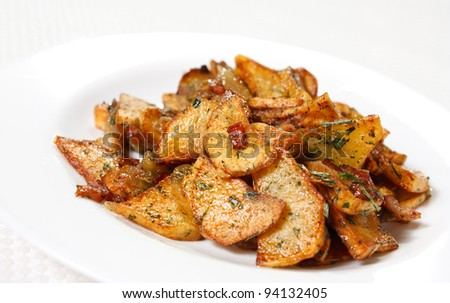 Potato wedges fried in oil on a plate. Golden and crispy