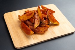 Potato wedges on a board. On a dark background