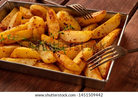Potato wedges, oven roasted, with thyme, a close-up in a baking tray, with two forks