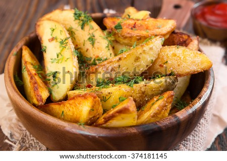 Potato wedges with dill in wooden bowl on wooden background Stock photo ©