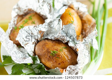 potatoes baked in foil with herbs, close-up